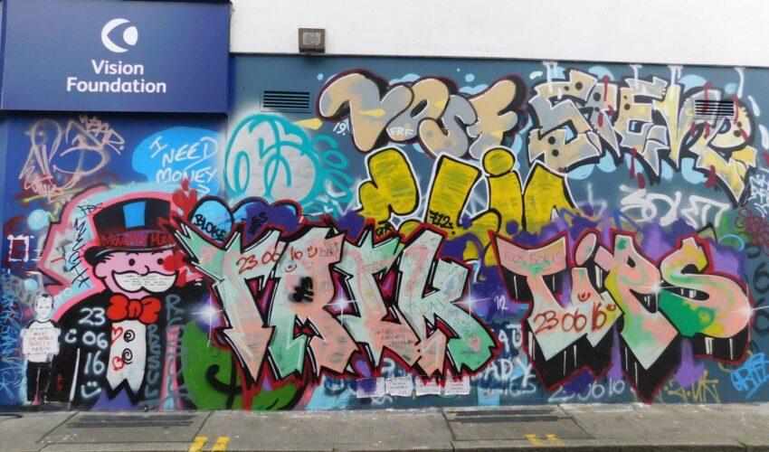 a colourful graffiti mural on the wall of the Vision Foundation Portobello Road shop