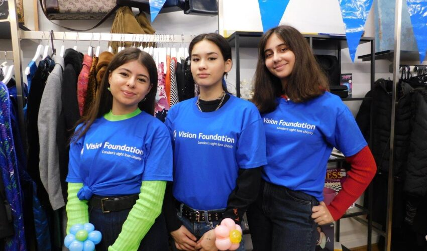 Three young women volunteers stand together in bright blue Vision Foundation t-shirts