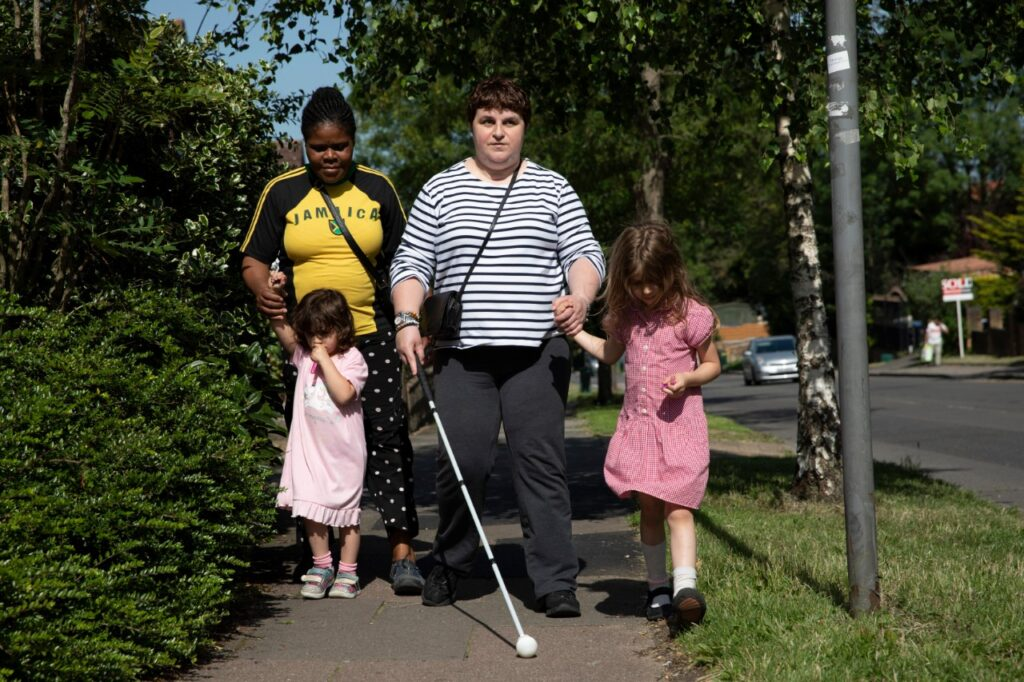 Charmaine uses her cane to guide her as she walks her two daughters home from school with their childminder Rita.