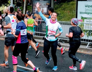 A Team GLFB runner waves to the camera as she runs the London Marathon