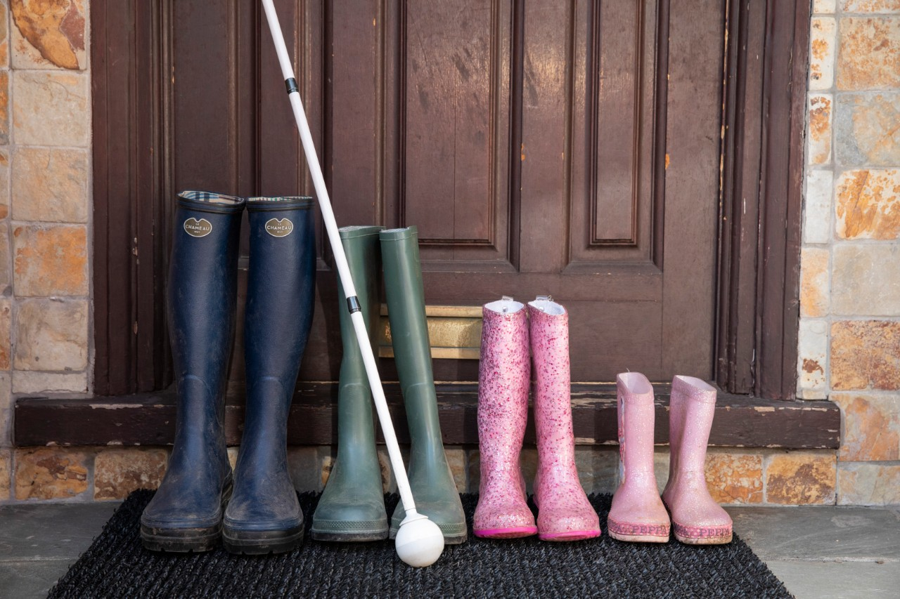 four sets of colourful wellington boots sit lined up in descending order outside a front door with a long white ball cane alongside.