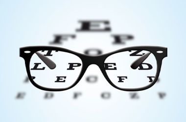 a pair of glasses are in front of a sight test chart with the letters in focus through the lenses of the glasses
