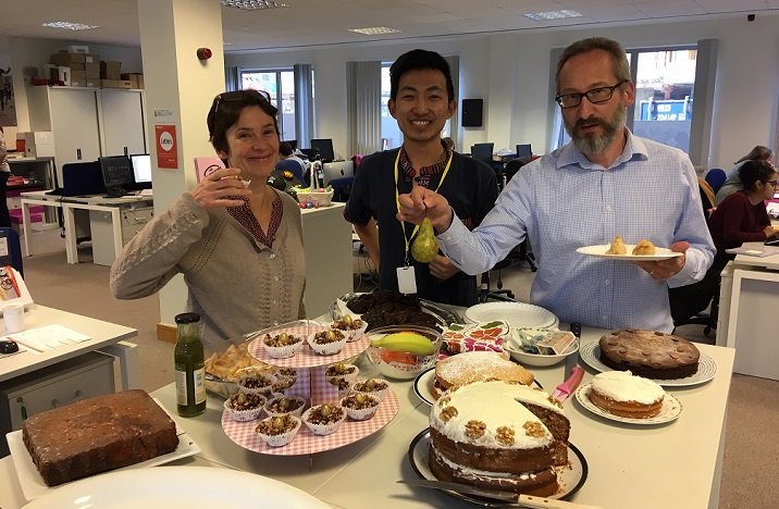 Office workers enjoying a cake sale with a number of cakes and cupcakes
