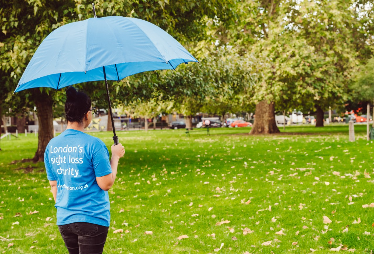 a woman wearing a Vision Foundation t-shirt stands holding an umbrella