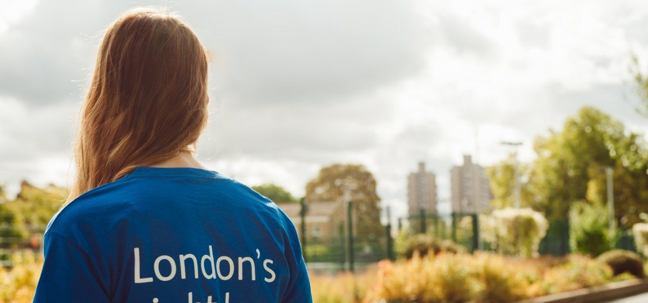 """A young woman stands with her back to us in a London park with the words """"London's sight loss charity"""" printed on the back of her t-shirt."""