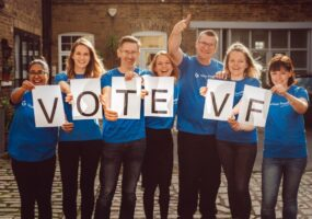 Vision Foundation staff in blue t-shirts holding up letters spelling VOTE VF
