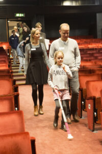 8 year old Eleanor walks with her cane into the theatre stalls with her mum and dad