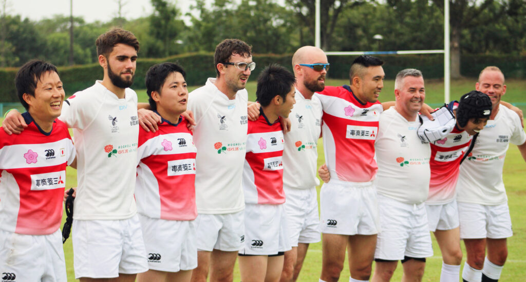 England and Japanese VI rugby players stand arm in arm