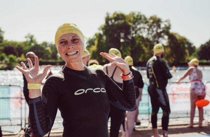 Image shows a lady smiling with her hands in the air after taking part in the Swim Serpentine