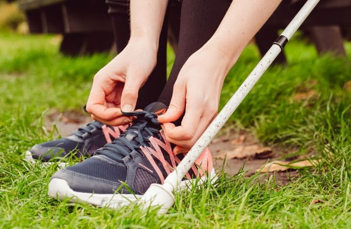 Image shows a woman tying the laces of black and pink trainers before her run. Next to her foot, a white cane is visible.
