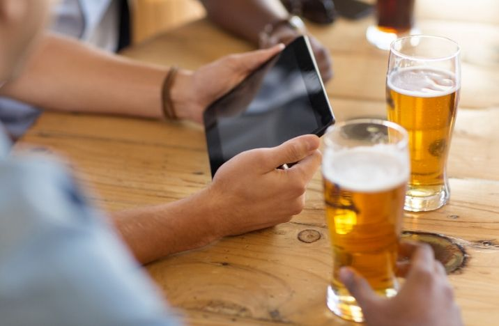Image shows a gentleman taking part in a pub quiz on his iPad whilst drinking a pint of beer.