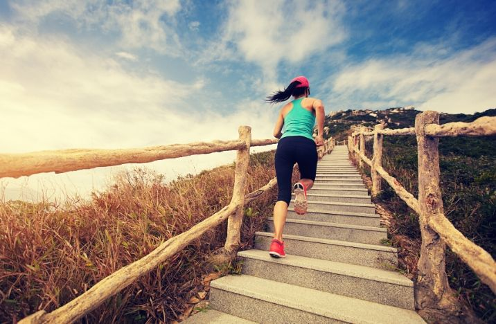 Image shows a lady running up an outdoor staircase in sportswear.