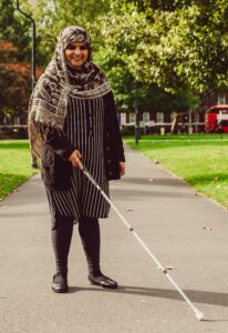 Image shows Khafsa walking with a white cane in a sunny park.