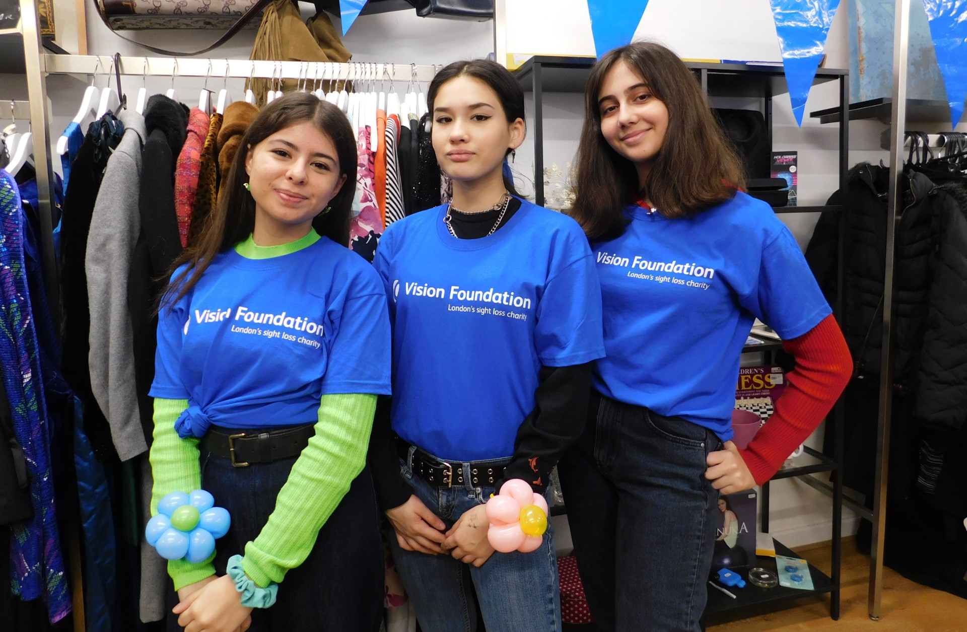 three shop volunteers pose wearing blue Vision Foundation t-shirts