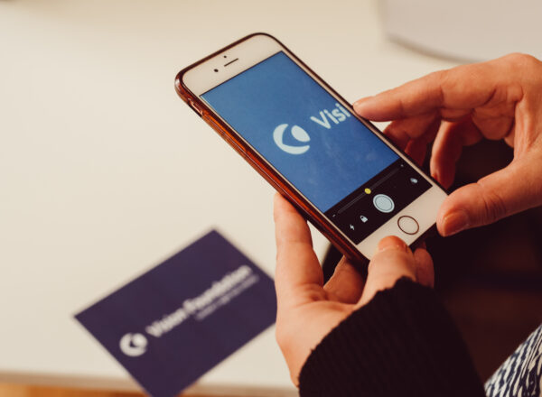 Image shows Khafa using an iPhone to read the Vision Foundation logo