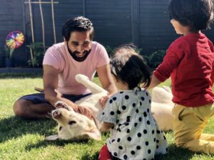 Image shows Amit playing in the garden with his two children and guide dog, Kika.