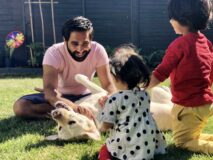 Image shows Amit playing with his two children and guide dog, Kika, in the garden.