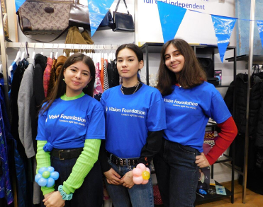 Three young women pose in a charity shop wearing blue Vision Foundation t-shirts