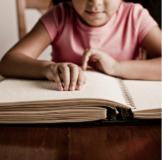 Child reading braille book