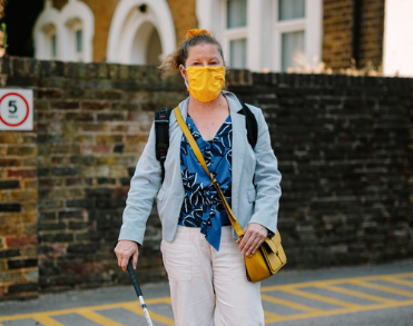 A woman with a face mask walking down the street