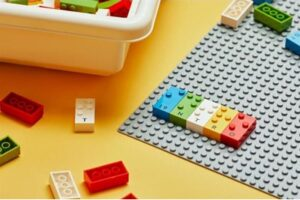 coloured lego bricks on a grey lego board. Each brick as braille dots on top
