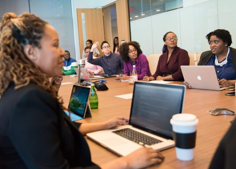A group of people sitting at the conference room table and interacting with others