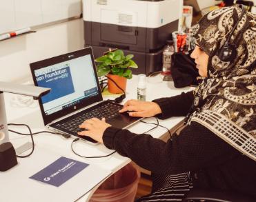 Khafsa sat at desk using access technology