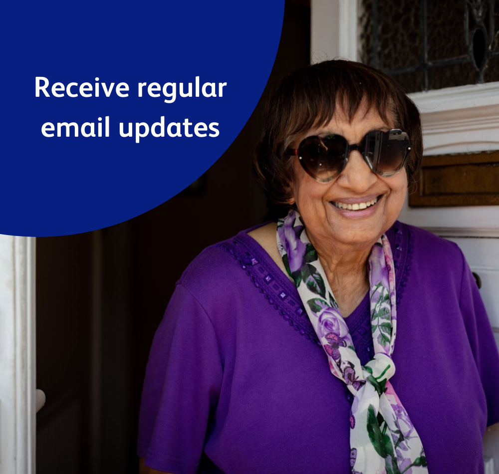 Image reads 'Receive regular email updates,' and shows a lady, Mary, who was supported by the Vision Foundation during the covid-19 crisis. Mary stands smiling on her doorstep.