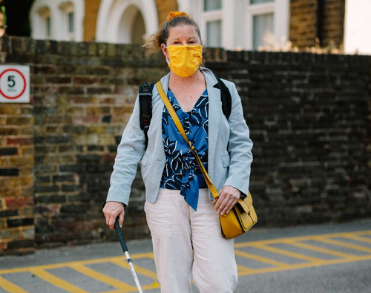 A lady, Odette, walking down the street with a white cane. Odette wears an orange face mask due to the Covid-19 pandemic.