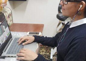 A profile photo of Rubab Rizvi using laptop at the desk