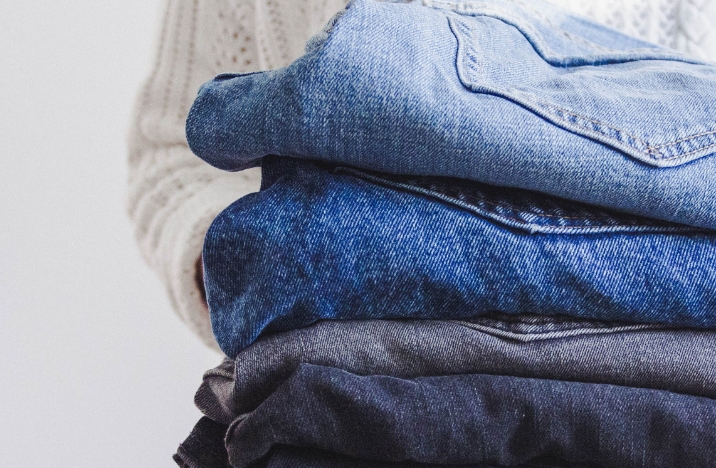 a bunch of folded denim jeans