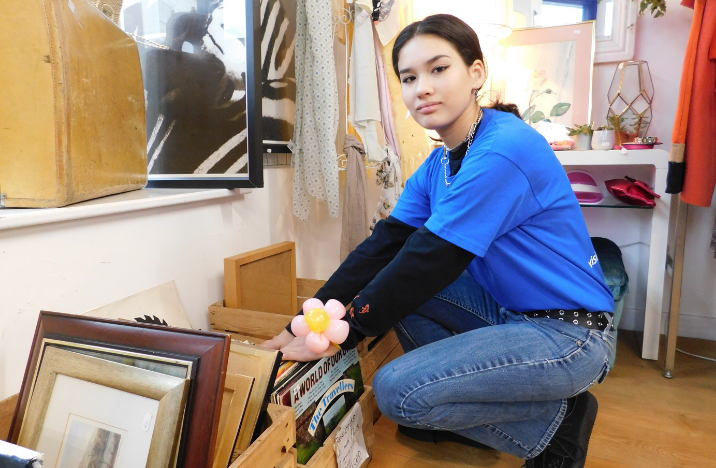 A young lady working as a volunteer in charity shop wearing Vision Foundation blue t-shirt