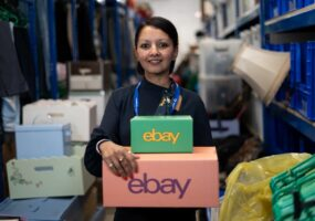 Brinda stands in the warehouse holding two coloured eBay boxes