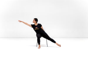 Dosti Dancer sits on chair and reaches to the right