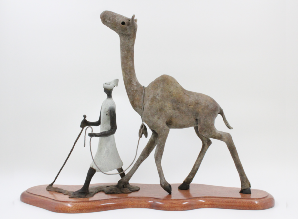 Terry Mathews' carefully crafted bronze sculpture, depicting a herder in a white garment leading a camel.