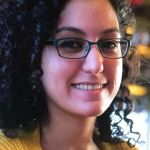 Elnaz smiling for a photo, wearing her glasses. She has curly salt and peppered black hair, brown eyes, and olive skin.