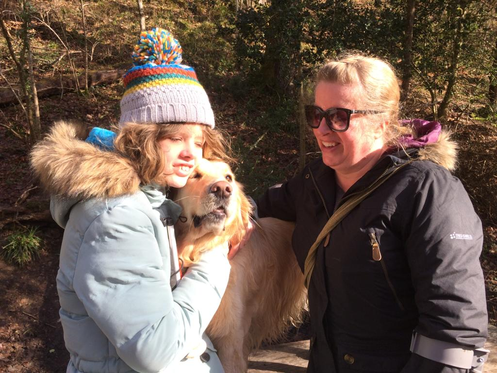 Image shows Chloe and her mum Jane smiling in the woods. Chloe is cuddling her golden buddy dog, Sapphire.