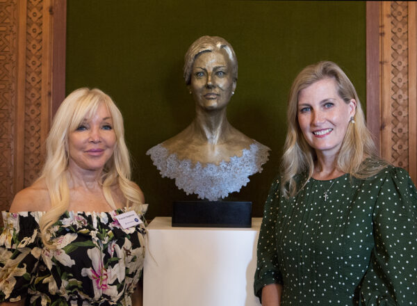 HRH The Countess of Wessex and sculptor, Frances Segelman stood either side of the newly unveiled bronze bust sculpture of HRH. The sculpture is bronze in colour, showing HRH with a tidy up-do and a relaxed face. There are hints of colour in her eyes and lips and a baby blue lace sculpted around her neckline.