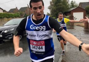 Gregg and Ian are taking part in 2020's virtual London Marathon. In this image they've swapped the crowds of supporters for some friendly neighbours, just out of shot are two arms reaching out to give the runners a high five.
