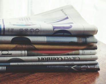 A stack of printed newspapers on a wooden table