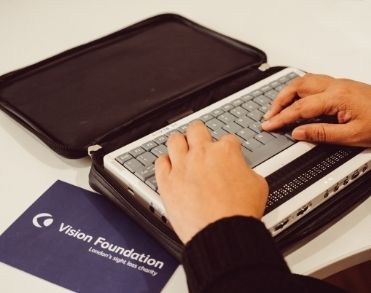 An image of a person raising their hands on a braille keyboard