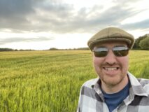 Chris standing in front of a field of wheat. The corn is turning golden and it's partially cloudy day. You can see some bright sunshine behind grey clouds. Chris is wearing a flat cap, sunglasses and a checked shirt over a blue tshirt.