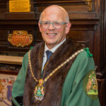 Image shows Ian Davies an white man with white hair and glasses. He is wearing the robes and livery of the Company